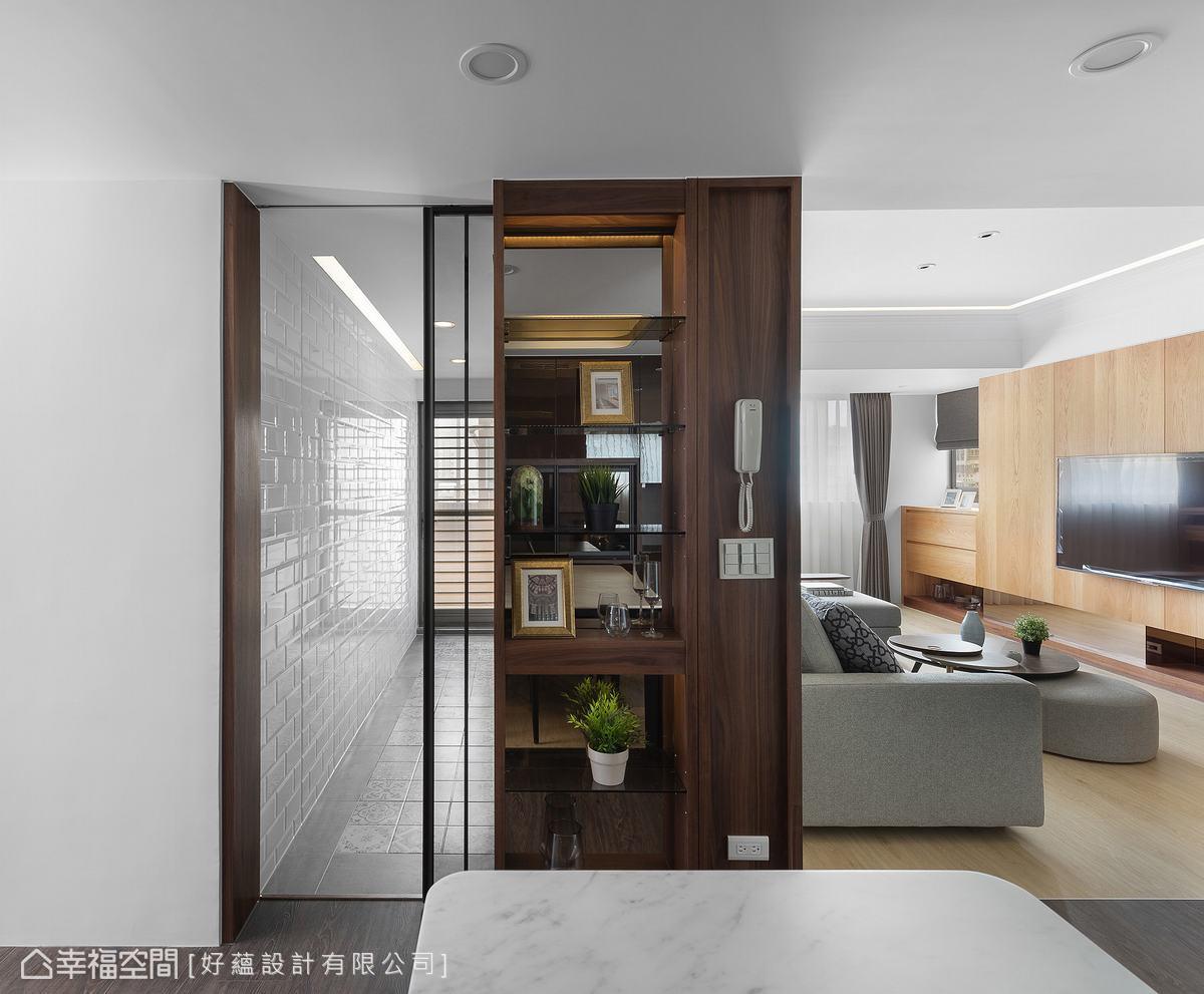 客廳與廚房之間配置展示櫃,利用櫃底的鏡面延伸空間感,一旁廚房的茶鏡拉門也增添場域的寬敞尺度。