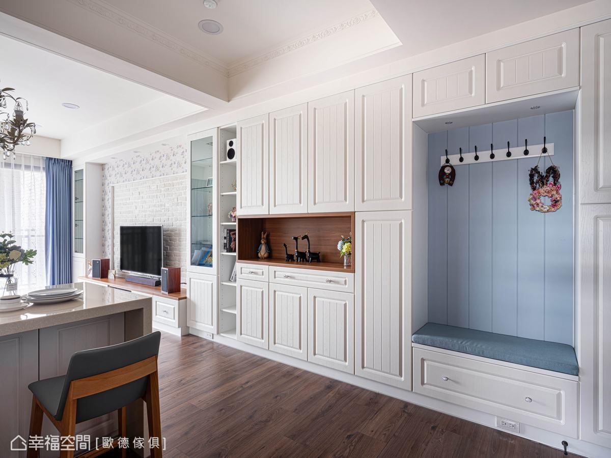 進門右側置入大片櫃體,歐德傢俱設計師高從硯穿插置物平台與穿鞋椅區,減少櫃體的沉重感,同時留給屋主佈置的空間。