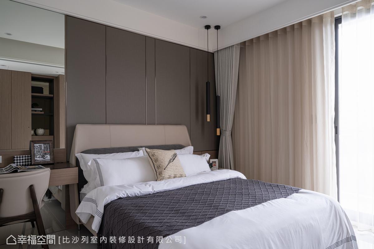 2樓另一處次臥床頭運用繃布搭配木皮,於細節處鑲以鍍鈦金屬描繪出線條,綴以具金色元素的吊燈,形塑出低調微奢表情。
