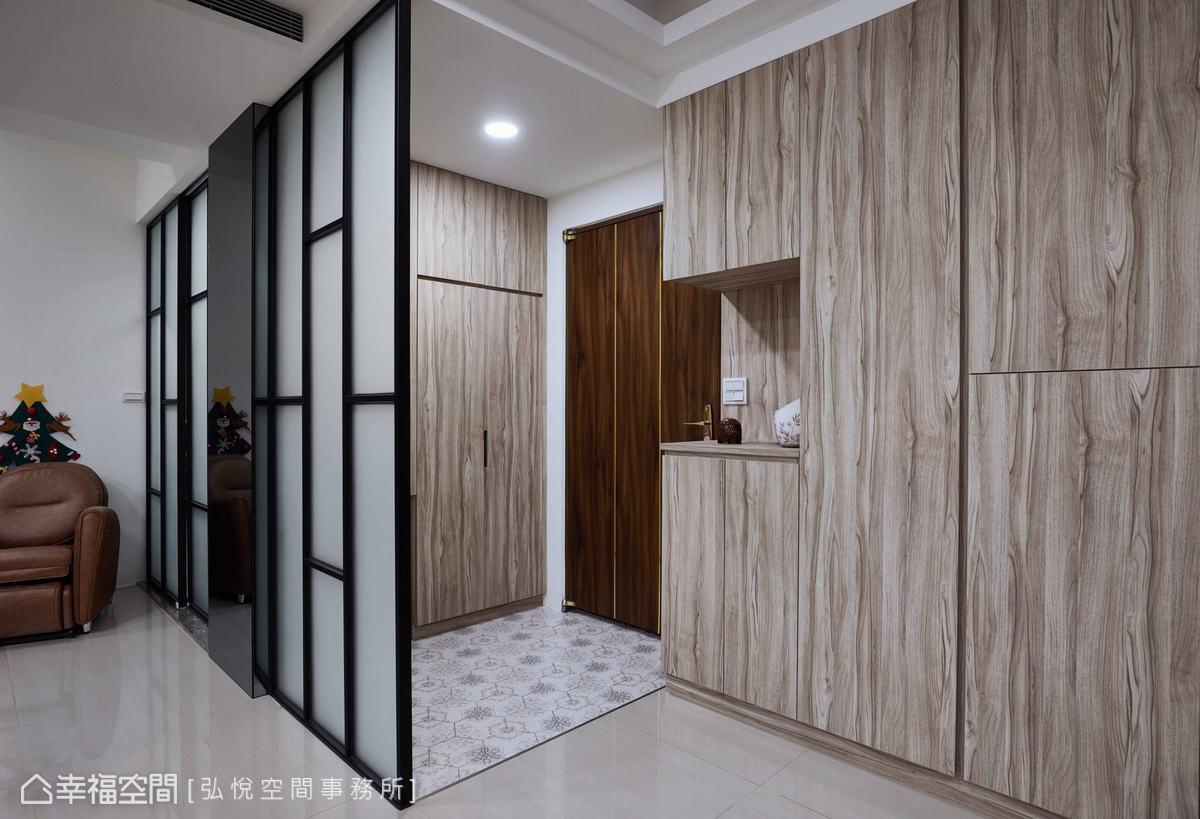 設計師以鐵件、玻璃,結合系統櫃,並搭配六角磚地坪,圍塑機能與美型兼具的玄關區域。