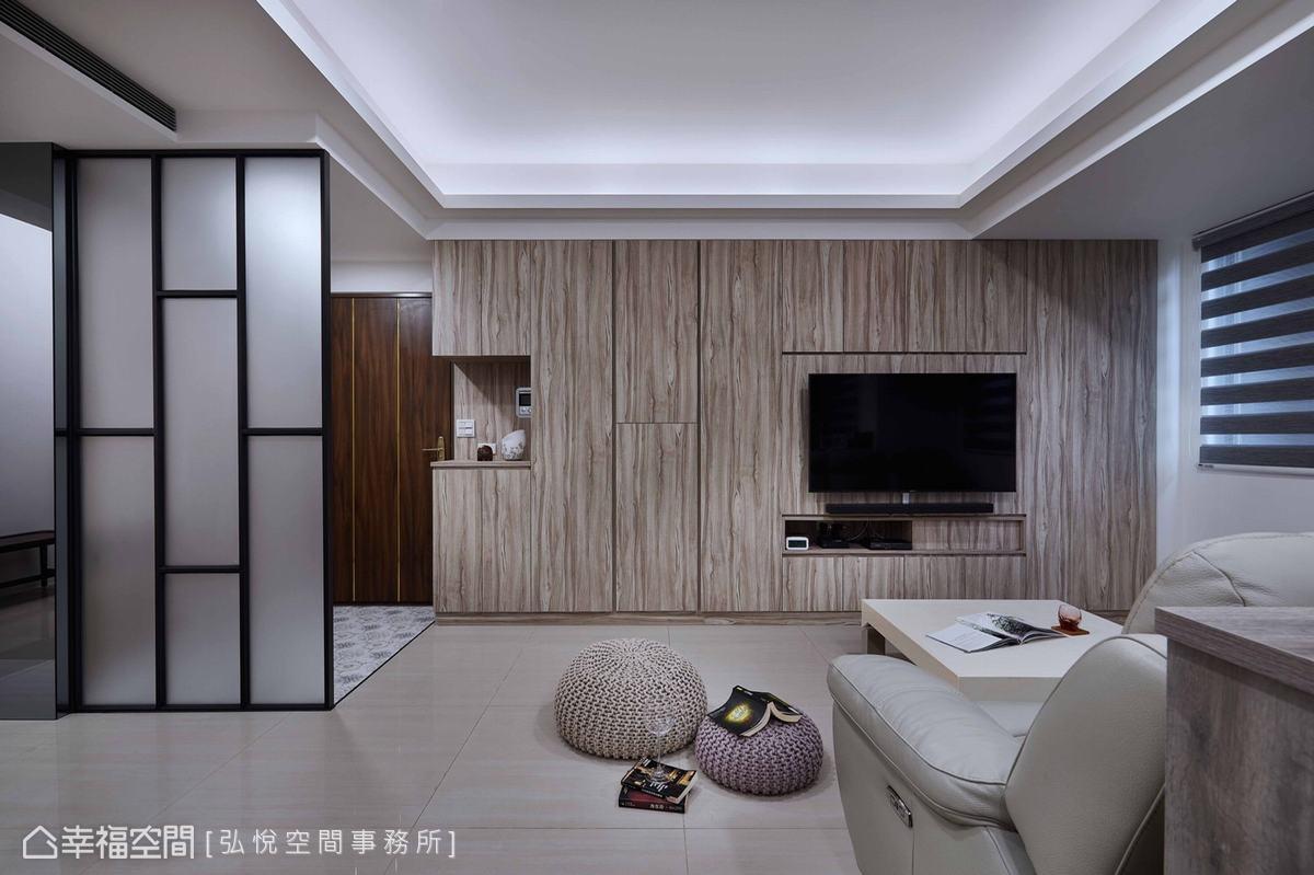 系統櫃由玄關延伸至電視牆,提供大量收納空間,木質紋理為公領域鋪敘質樸簡歛調性。
