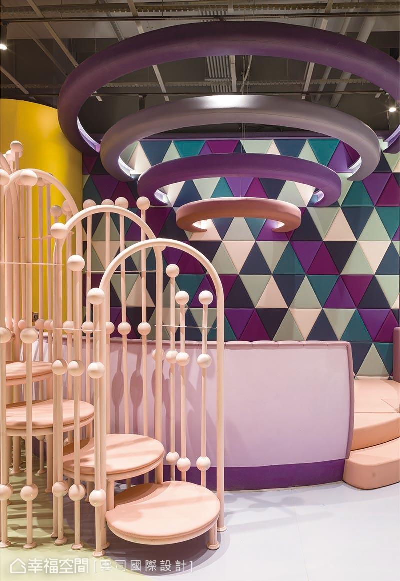 粉紅色樓梯以孩子身高打造、彷彿像是專屬祕密通道;三角繃布牆面則是跳床區,頭頂一圈圈的造型,就像是幽浮發射的光圈般,刺激孩子無限想像。