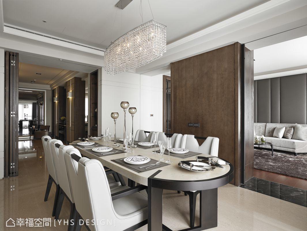 位於廊道底端的餐廳空間,對稱式的端景櫃給人正式的餐敘氛圍,船型木質考漆餐桌與水晶燈造型呼應,於奢華氛圍中保留觸感舒適。