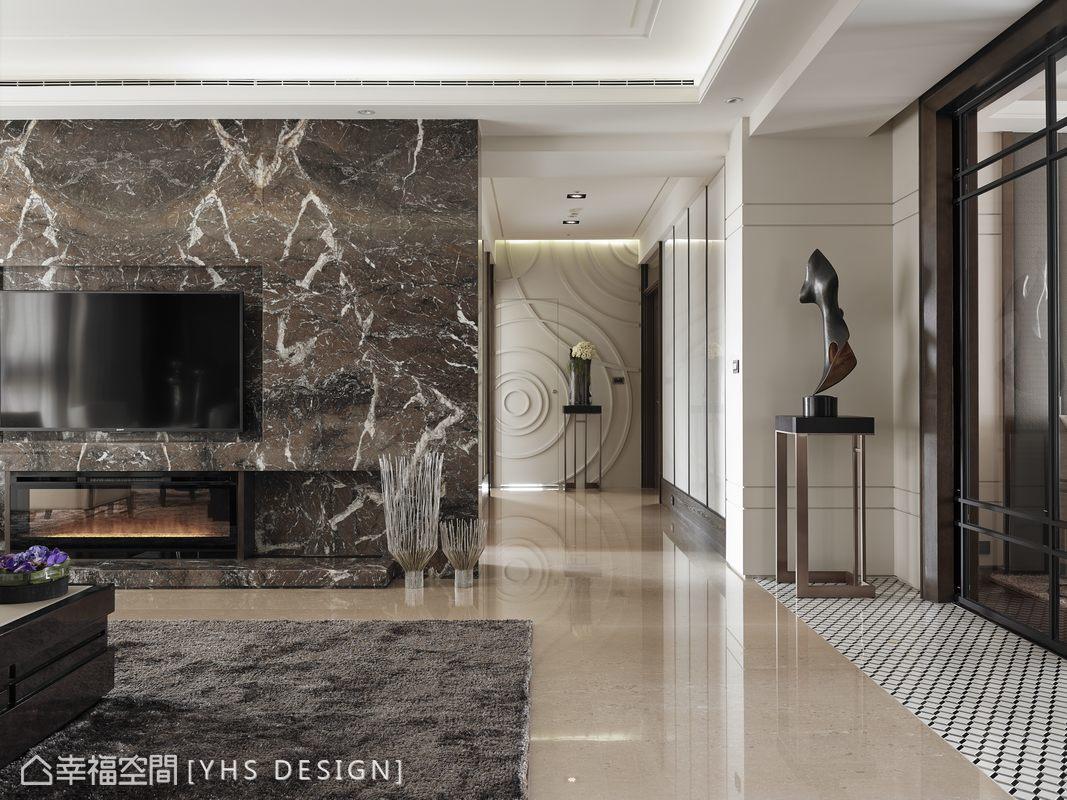 整合於客廳主牆側的空間動線,以鋼琴烤漆表現直向線條的分割與盈亮光澤,端景納入水波漣漪的造型,藏起客用衛浴門扇。